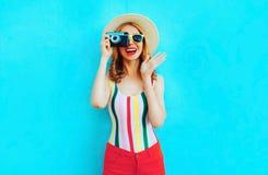 拿着在夏天草帽的五颜六色的愉快的微笑的年轻女人减速火箭的照相机获得在蓝色wal的乐趣 免版税库存图片
