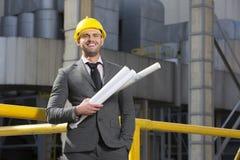 拿着在大厦之外的微笑的年轻男性建筑师画象图纸 图库摄影