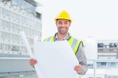 拿着在大厦之外的愉快的建筑师图纸 免版税库存图片