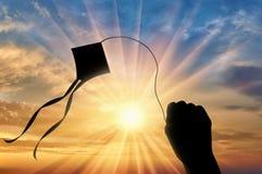 拿着在天空日落的手风筝 免版税图库摄影