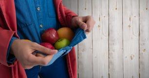 拿着在套头衫的人苹果反对木头 库存图片