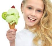 拿着在奶蛋烘饼锥体的俏丽的女婴孩子冰淇凌与粗锉 免版税库存照片