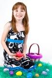 在假草的年轻女性开会用复活节彩蛋 免版税库存图片