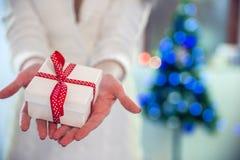 拿着在她前面的美丽的女孩一个圣诞节礼物 站立在新年树附近的圣诞老人帽子的愉快的妇女 库存照片