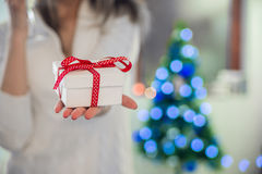 拿着在她前面的美丽的女孩一个圣诞节礼物 站立在新年树附近的圣诞老人帽子的愉快的妇女 免版税库存图片