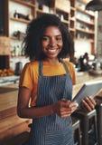 拿着在她的一个女性所有者的微笑的画象数字片剂 免版税库存照片