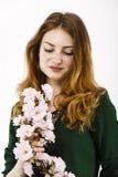 拿着在她的一名美丽的红发妇女的画象一朵花 库存图片