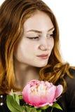拿着在她的一名美丽的红发妇女的画象一朵花 免版税库存照片