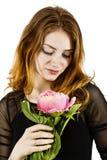 拿着在她的一名美丽的红发妇女的画象一朵花 免版税图库摄影