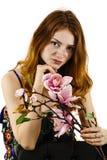 拿着在她的一名美丽的红发妇女的画象一朵花 免版税库存图片
