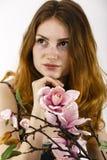 拿着在她的一名美丽的红发妇女的画象一朵花 图库摄影