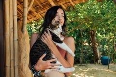 拿着在她的与非的画象美丽的妇女猫 有猫的可爱的浅黑肤色的男人 库存图片