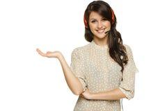 拿着在她的开放掌上型计算机的耳机的妇女空的复制空间 免版税库存图片
