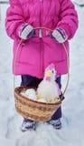 拿着在她的手上一个篮子用复活节彩蛋和雄鸡,冬天的天的小女孩在街道上的在公园 免版税库存照片