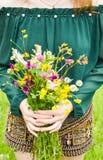 拿着在她的手上与多彩多姿的野花的女孩美丽的花束 令人惊讶的束在自然的wilf花 免版税库存照片