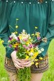 拿着在她的手上与多彩多姿的野花的女孩美丽的花束 令人惊讶的束在自然的wilf花 库存图片