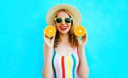 拿着在她的手上两个切片在草帽的橙色果子的夏天画象愉快的微笑的妇女在五颜六色的蓝色 库存照片
