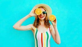 拿着在她的手上两个切片橙色果子的夏天画象微笑的妇女掩藏她的眼睛在五颜六色的蓝色的草帽 库存图片