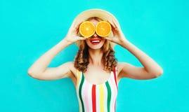 拿着在她的手上两个切片橙色果子的夏天画象愉快的微笑的妇女掩藏她的眼睛在五颜六色的蓝色的草帽 免版税库存照片