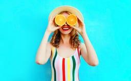 拿着在她的手上两个切片橙色果子的夏天画象愉快的微笑的妇女掩藏她的眼睛在五颜六色的蓝色的草帽 免版税库存图片