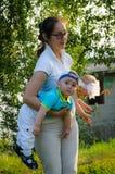 拿着在她的手上小孪生的一个年轻母亲 免版税库存照片