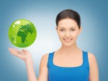 拿着在她的手上的妇女绿色地球 免版税图库摄影
