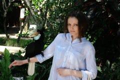 拿着在她的手上的美丽的女孩一只大鸟Toucan 免版税库存照片