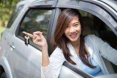 拿着在她的手指的年轻亚裔妇女一辆关键汽车在wi之外 免版税库存照片