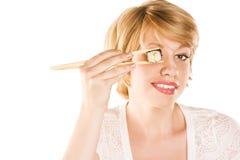 拿着在她的眼睛的妇女的图片寿司卷 免版税库存图片