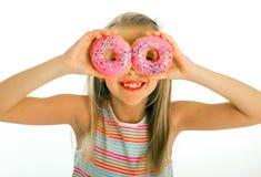 拿着在她的眼睛的年轻美好的愉快和激动的白肤金发的女孩8或9岁两个油炸圈饼看通过他们使用快乐 免版税库存图片