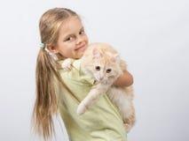 拿着在她的胳膊的六岁的女孩一只猫 免版税库存照片