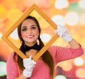 拿着在她的面孔前面的逗人喜爱的女孩小丑笑剧特写镜头画象木制框架 免版税库存照片