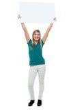 拿着在她的题头之上的妇女广告董事会 免版税库存图片