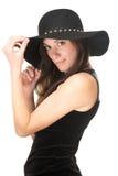 拿着在她的头的俏丽的妇女黑帽会议 库存照片