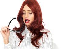 拿着在她的嘴的年轻女商人玻璃看起来有关和殷勤 库存图片