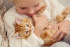 拿着在姜手上的逗人喜爱的小女孩一只小猫 免版税库存照片