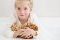 拿着在姜手上的逗人喜爱的小女孩一只小猫 免版税库存图片