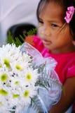 拿着在婚礼庆祝的桃红色礼服的逗人喜爱的小女孩白花花束 婚礼的一点女花童 免版税库存图片