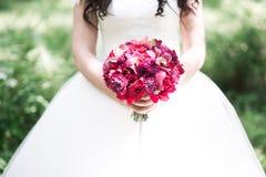 拿着在婚礼的新娘婚礼花束 免版税库存图片