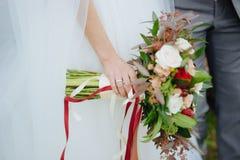 拿着在婚礼的白色礼服的新娘婚礼花束 库存照片