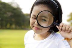 拿着放大镜的女孩 免版税库存照片