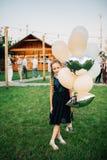 拿着在室外的女孩气球 非洲裔美国人气球美丽的生日蛋糕庆祝巧克力杯子楼层女孩藏品家当事人当前坐的微笑的包围的时间对年轻人 免版税库存图片