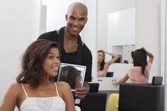 拿着在少妇后的美发师一个镜子 免版税库存图片