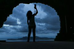 拿着在岩石的youn妇女的剪影一台照相机由s 图库摄影