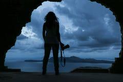 拿着在岩石的youn妇女的剪影一台照相机由s 免版税库存图片