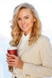 拿着在工休的微笑的美丽的女实业家咖啡 免版税库存图片