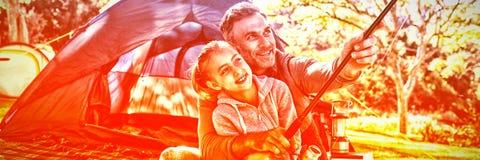 拿着在帐篷之外的父亲和女儿一根钓鱼竿 库存图片