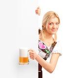 拿着在广告牌之后的德国女孩啤酒 免版税图库摄影