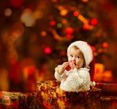 拿着在当前礼物的圣诞老人帽子的圣诞节婴孩红色球 免版税库存图片