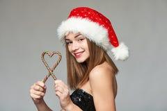拿着在心脏形状的圣诞老人帽子的女孩圣诞节糖果 库存图片